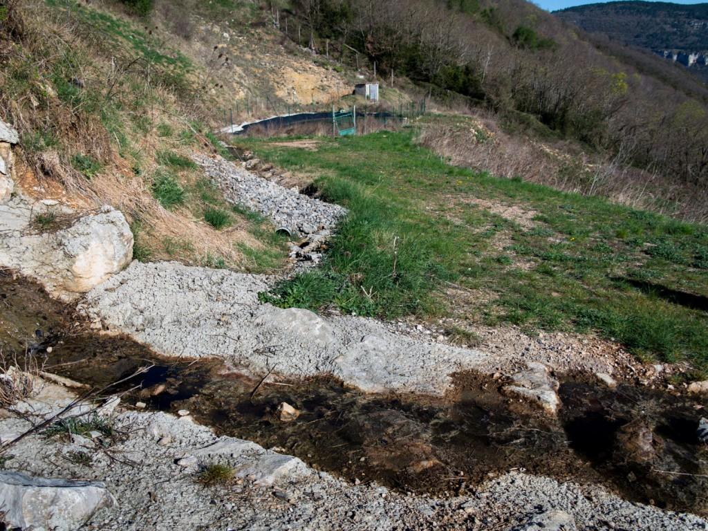 La tranchée au premier plan se jette directement au fond du ravin, vers la rivière. Au fond, le bassin de rétention.
