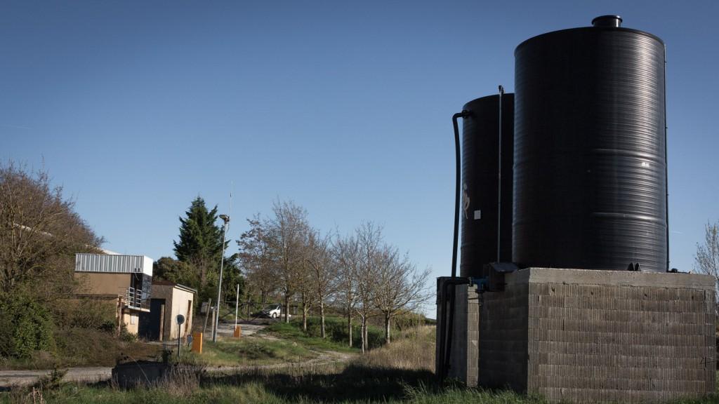 Entrée de l'ex-décharge. A droite, les cuves dans lesquelles les eaux à traiter sont stockées avant récupération. A gauche, des locaux abandonnés.